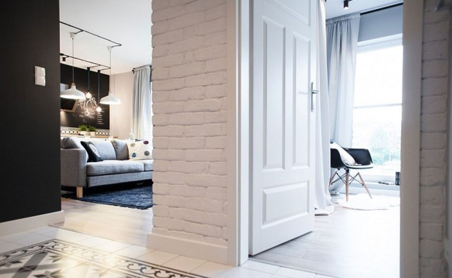 Exposed-brick-walls-of-the-Chmielna-Apartment-in-white